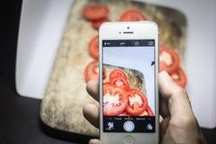 Amis à l'aide des smartphones pour prendre des photos de nourriture Photographie stock libre de droits