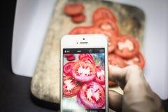 Amis à l'aide des smartphones pour prendre des photos de nourriture Photo stock