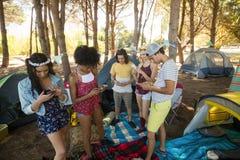Amis à l'aide des téléphones portables tout en se tenant au terrain de camping Photos stock