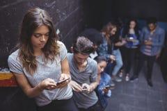 Amis à l'aide des téléphones portables tout en se tenant prêt le mur Images libres de droits