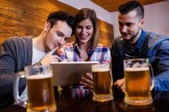 Amis à l'aide du comprimé numérique au restaurant Photo stock