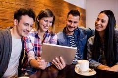 Amis à l'aide du comprimé numérique dans le restaurant Photo stock