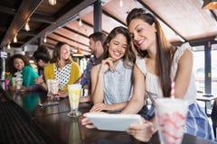 Amis à l'aide du comprimé numérique dans le restaurant Image libre de droits