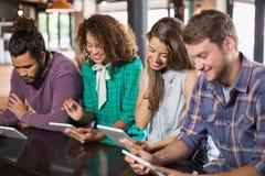 Amis à l'aide du comprimé numérique dans le restaurant Image stock