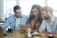 Amis à l'aide du comprimé numérique et de l'ordinateur portable dans le café Images stock