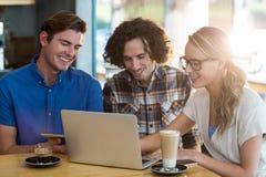 Amis à l'aide du comprimé numérique et de l'ordinateur portable dans le café Image libre de droits