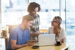 Amis à l'aide du comprimé numérique et de l'ordinateur portable dans le café Photos stock