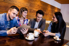 Amis à l'aide du comprimé numérique et du téléphone portable au restaurant Photo stock