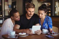 Amis à l'aide du comprimé numérique tout en prenant le petit déjeuner Photo libre de droits