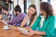 Amis à l'aide du comprimé numérique tout en se reposant dans le restaurant Photos stock