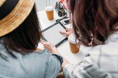 Amis à l'aide du comprimé numérique tout en se reposant en café Image stock