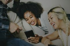 Amis à l'aide du smartphone ensemble à la maison Images libres de droits