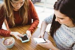 Amis à l'aide du smartphone et ayant le café Photographie stock