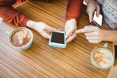 Amis à l'aide du smartphone et ayant le café Photos stock