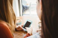 Amis à l'aide du smartphone et ayant le café Photos libres de droits