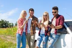 Amis à l'aide du téléphone intelligent causant la transmission de messages extérieure de personnes de campagne Photo libre de droits