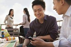 Amis à l'aide du téléphone portable au barbecue de dessus de toit Photo stock