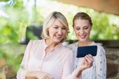 Amis à l'aide du téléphone portable au restaurant Images libres de droits