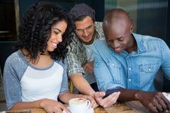 Amis à l'aide du téléphone portable dans le café Photo libre de droits