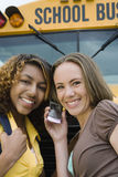 Amis à l'aide du téléphone portable en l'autobus scolaire Photographie stock