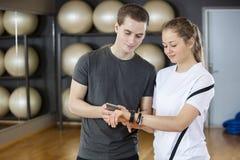 Amis à l'aide du téléphone portable et de la montre intelligente dans le gymnase Images stock
