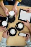 Amis à l'aide du téléphone portable et du comprimé numérique tout en ayant la tasse de café Photos stock