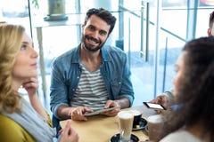 Amis à l'aide du téléphone portable et du comprimé numérique tout en ayant la tasse de café Image libre de droits
