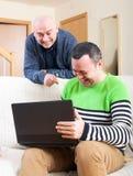 Amis à l'ordinateur dans la maison Photographie stock libre de droits