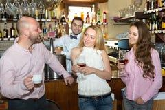 Amis à la barre avec le barman Images stock