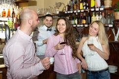 Amis à la barre avec le barman Images libres de droits