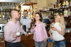 Amis à la barre avec le barman Image stock