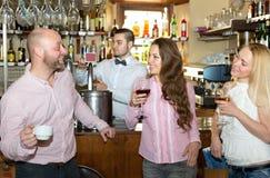 Amis à la barre avec le barman Photographie stock libre de droits