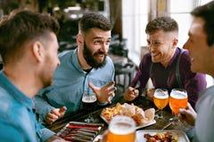 Amis à la bière de dîner et à la nourriture potables de consommation au restaurant Photo stock