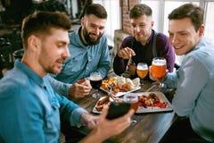 Amis à la bière de dîner et à la nourriture potables de consommation au restaurant Image libre de droits