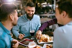 Amis à la bière de dîner et à la nourriture potables de consommation au restaurant Images stock
