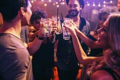 Amis à la boîte de nuit célébrant avec des boissons Images stock