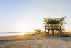 Amis à la hutte de plage de coucher du soleil Photographie stock