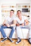 Amis à la maison jouant le jeu vidéo Image stock