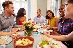 Amis à la maison s'asseyant autour du Tableau pour le dîner Photographie stock libre de droits
