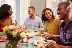 Amis à la maison s'asseyant autour du Tableau pour le dîner Image libre de droits