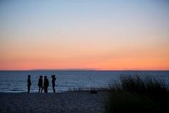 Amis à la plage dans le coucher du soleil Image libre de droits