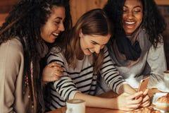 Amis à un café regardant le téléphone portable Image libre de droits
