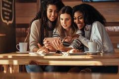 Amis à un café regardant le téléphone portable Photo stock