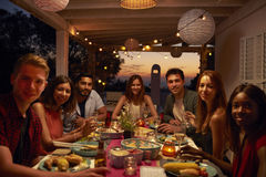 Amis à un dîner sur un patio regardant à l'appareil-photo Image libre de droits