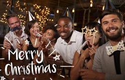 Amis à une partie dans une barre avec le message de Joyeux Noël Image stock