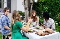 Amis à une partie extérieure dans le jardin avec la nourriture et la boisson Images libres de droits