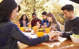 Amis à une table à un barbecue disant la grâce avant la consommation Images libres de droits