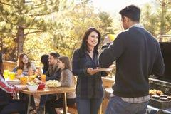Amis à une table et à deux parlant par le gril à un barbecue Photographie stock