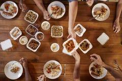Amis à une table partageant la vue à emporter et aérienne chinoise Photographie stock libre de droits