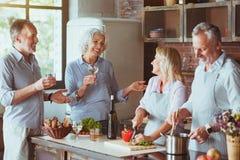 Amis âgés gais faisant cuire le dîner ensemble Photo stock